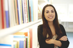 Woman posing in library with arms crossed. Stock Image