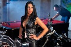 woman posing near motorbikes, man playing billiards Royalty Free Stock Photo