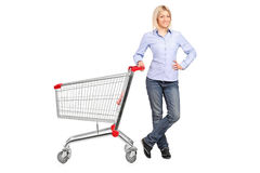 Woman posing next to an empty shopping cart Royalty Free Stock Images
