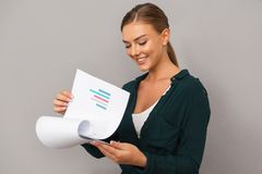 Woman posing over grey wall background holding clipboard with graphics. Image of business young woman posing over grey wall background holding clipboard with royalty free stock images