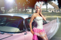 Woman posing over retro car. Beautiful woman in pink skirt, white corset and elegant hat  posing over retro car Royalty Free Stock Images