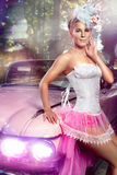 Woman posing over retro car. Beautiful woman in pink skirt, white corset and elegant hat  posing over retro car Royalty Free Stock Photos