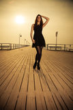Woman posing on pier at sunrise Stock Images