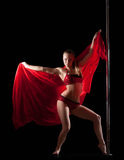 Woman posing in pole dance with red silk fabric Stock Image