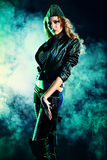 Woman posing. Portrait of a beautiful woman posing in a military style over dark background Royalty Free Stock Photo