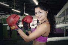 Woman posing ready to strike in the ring. Picture of young Indian boxer looking at the camera while posing ready to strike in the ring Royalty Free Stock Photos