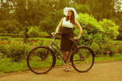 Woman posing with retro bicycle in the park Royalty Free Stock Photos