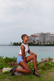 Woman posing on rocks by the water Stock Photo