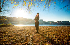 Woman posing on sandy river beach at sunny autumn day Royalty Free Stock Photo