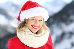 Woman posing with santa hat in christmas. Portrait of a happy woman posing with santa claus hat in christmas holidays with a snowy mountain in the background stock photo