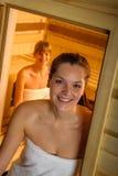 Woman posing at sauna in health spa. Sweaty brunette women leaving sauna luxury spa center Royalty Free Stock Photos