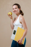 Woman posing with scales and apple Stock Image