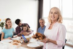 Woman posing with smoked chicken in hands. Now she will serve her dinner for her family. A women in a white cardigan is holding a baked chicken in a dish Stock Image