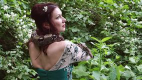 Woman posing with a snake around her neck stock video
