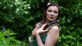 Woman posing with a snake around her neck stock footage