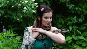 Woman posing with a snake around her neck stock video footage