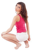 Woman posing in squatting position Royalty Free Stock Image