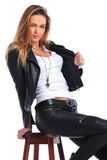 Woman posing in studio arranging her leather jacket while seated Royalty Free Stock Images