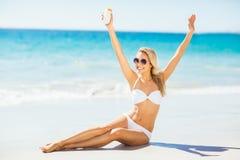 Woman posing with sun cream on beach Stock Image