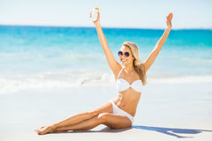 Woman posing with sun cream on beach Stock Photography