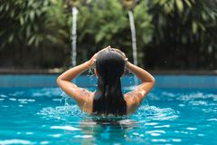 Woman posing in swimpool stock images