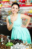 Woman posing to photographer with lollypop. Portrait adult girl posing to photographer with lollypop at candies shop Stock Photo