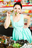 Woman posing to photographer with lollypop. Smiling adult girl posing to photographer with lollypop at candies shop Royalty Free Stock Images