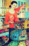 Woman posing to photographer picking different candies Royalty Free Stock Photo