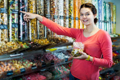 Woman posing to photographer picking different candies Stock Photography