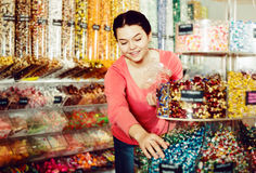Woman posing to photographer picking different candies Stock Photos