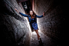 Woman posing between two brick walls at night Stock Photos