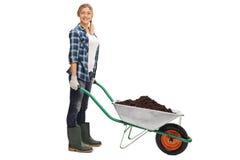 Woman posing with wheelbarrow full of dirt Stock Photo