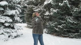 Woman is posing in winter forest, beautiful landscape with snowy fir trees stock video footage