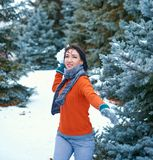 Woman is posing in winter forest, beautiful landscape with snowy fir trees. Making snowball stock photos