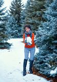 Woman is posing in winter forest, beautiful landscape with snowy fir trees. Making snowball royalty free stock photography
