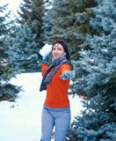 Woman is posing in winter forest, beautiful landscape with snowy fir trees. Making snowball stock photo