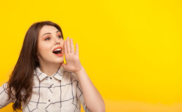 Woman posing on yellow and calling. Young model in shirt holding hand near mouth calling on yellow background royalty free stock photos