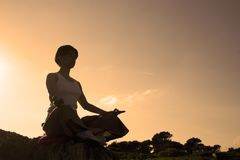 Woman in position of the makin. Woman making of yoga at the sunset Royalty Free Stock Photography