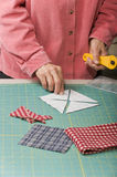 Woman positioning cut triangle fabric. A quilter lays out four triangle pieces of fabric wrong side up Royalty Free Stock Photography