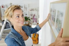 Free Woman Positioning Picture Frame On Wall Royalty Free Stock Photography - 160148717