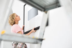 Woman positioning picture frame on wall Stock Photo