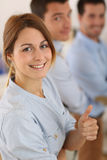 Woman with a positive look standing with businessteam. Cheerful girl in office showing thumbs up Royalty Free Stock Photography