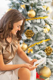 Woman with postcard sitting near christmas tree Stock Photo