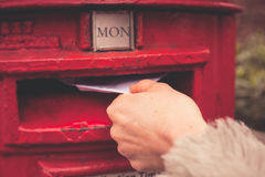 Woman posting letter. Closeup on a woman's hand as she is posting a letter Royalty Free Stock Images