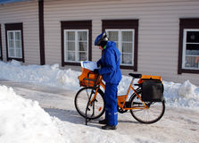 Woman postman at work. PORVOO, FINLAND - MARCH 9, 2012. The woman postman delivering post to local people on the service bicycle March 9, 2012 in Porvoo, Finland royalty free stock image
