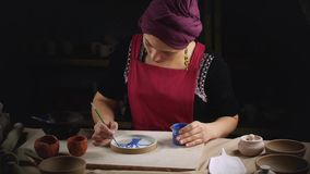 Woman Potter paints a plate made with his own hands. Manual work. Folk art.  stock video