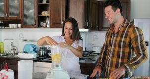 Woman Pour Water In Blender To Pineapple Talking With Man Couple In Kitchen Prepare Healthy Smoothie Juice Together stock video footage