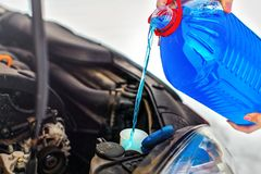 Woman pouring antifreeze car screen wash liquid into dirty car. From blue anti freeze water container royalty free stock photo
