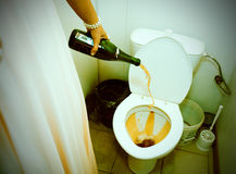 Woman pouring champagne in toilet Royalty Free Stock Photography
