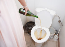 Woman pouring champagne in toilet Stock Photos